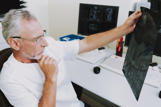 Älterer doktor radiologist thinking auf mri-bildern.