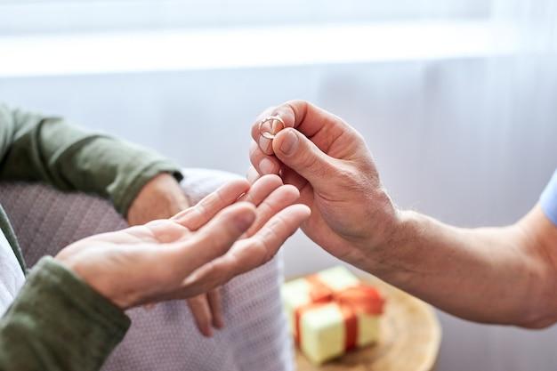 Älterer ehemann machte eine überraschung für seine frau, bitte sie, ein grauhaariger mann überreicht geschenk an ältere angenehm überraschte frau, geben ring. nahaufnahme hände
