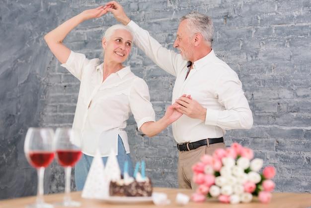 Älterer ehemann und frau, die an der geburtstagsfeier tanzt