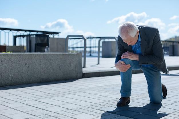 Älterer enttäuschter charismatischer mann, der schmerzendes knie berührt, negative emotionen zeigt und sich sorgen um seine gesundheit macht