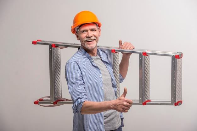 Älterer erbauer, der treppe hält
