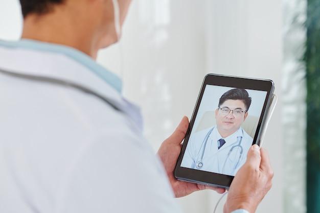 Älterer erfahrener allgemeinarzt auf dem bildschirm auf dem tablet-computer in den händen des arztes
