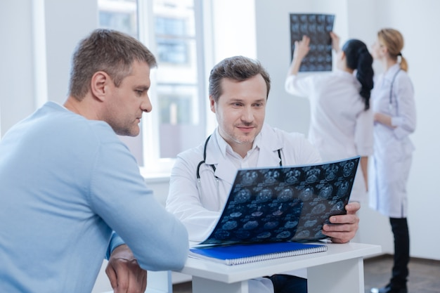 Älterer, erfahrener, selbstbewusster therapeut, der einen termin mit dem patienten genießt und den mrt-scan analysiert, während krankenschwestern gerne hinterher diskutieren