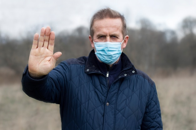 Älterer ernsthafter mann in der medizinischen sterilen maske auf seinem gesicht, das handfläche zeigt, stoppschild mit der hand gegen coronavirus ,. pandemie, virus, covid-19-konzept