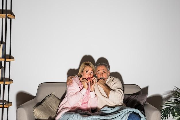 Älterer erschrockener mann, der mit frau umarmt und auf sofa fernsieht