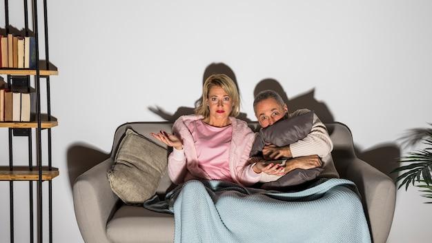 Älterer erschrockener mann nahe überraschter frau, die auf sofa fernsieht