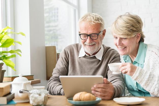 Älterer erwachsener, der digital-gerät-tablet-konzept verwendet