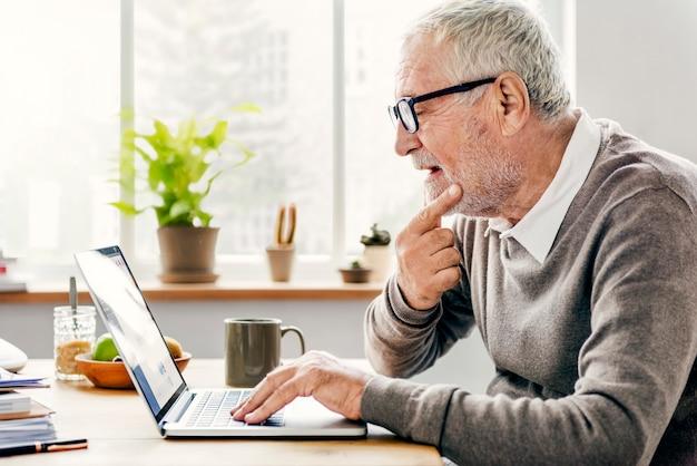 Älterer erwachsener, der laptop denkendes konzept verwendet