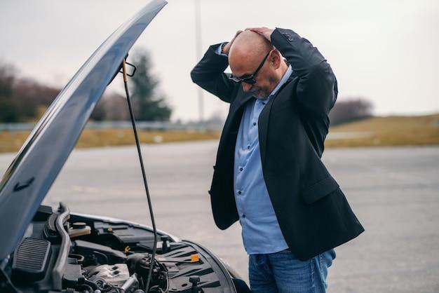 Älterer erwachsener mann, der hände auf kopf hält, während er vor geöffneter motorhaube seines autos steht.
