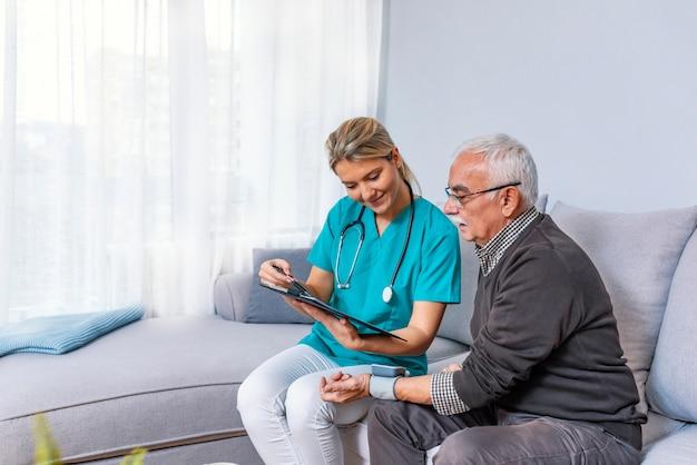 Älterer erwachsener mann, der von der ärztin lernt, um blutdruck-maschine zu benutzen.