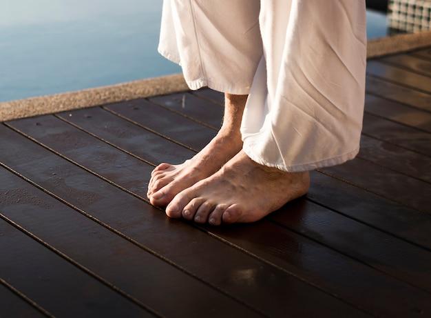 Älterer erwachsener übender yoga am pool
