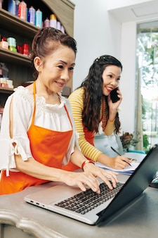 Älterer florist, der die bestellung über das formular auf der website des blumenladens annimmt, wenn ihre jüngere kollegin mit dem kunden telefoniert