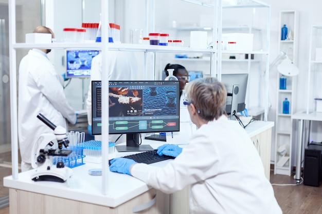 Älterer forscher, der menschliches adn mit software auf einem leistungsstarken computer entwickelt. leitender wissenschaftler im pharmazeutischen labor, der genetische forschung mit laborkittel mit team im hintergrund durchführt.