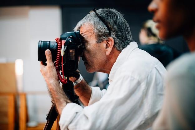 Älterer fotograf, der einen schuss macht