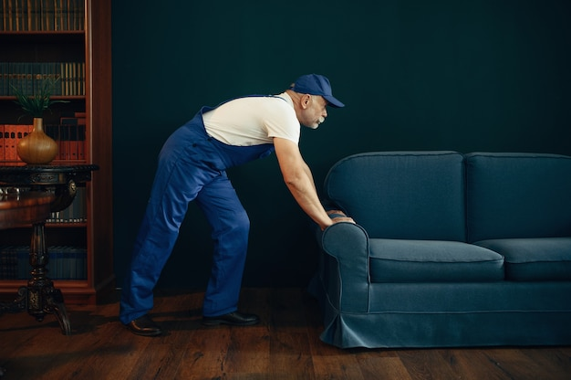 Älterer frachtmann in uniform bewegt sofa im home office. erwachsener lieferarbeiter, lieferung in mütze hält die couch drinnen und liefert service oder geschäft