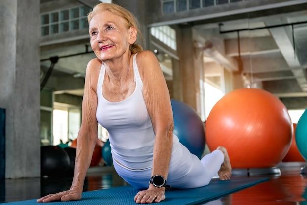 Älterer frau kaukasier, der yogaübung an der eignungsturnhalle tut.