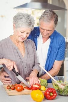 Älterer frauenausschnitt während mann, der in der küche umfasst