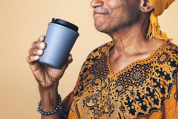 Älterer gemischter indischer mann, der kaffee aus einem bechermodell trinkt