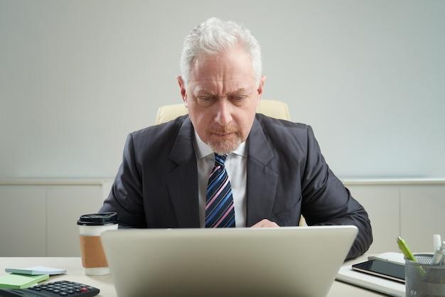Älterer geschäftsmann am arbeitsplatz