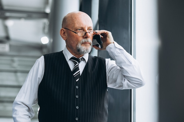 Älterer geschäftsmann, der am telefon im büro spricht