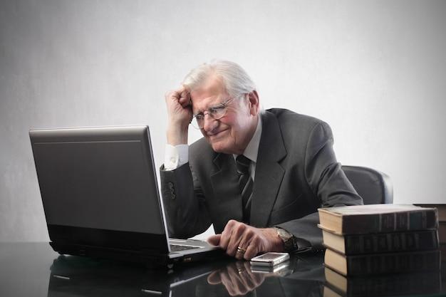 Älterer geschäftsmann, der an einem laptop arbeitet