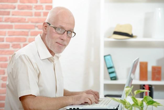 Älterer geschäftsmann, der an laptop-computer arbeitet