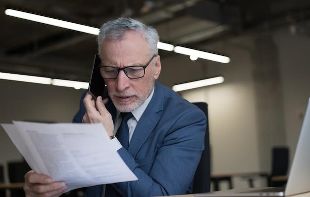 Älterer geschäftsmann, der auf handy spricht, vertrag liest, brainstorming arbeitet im büro. multitasking-konzept