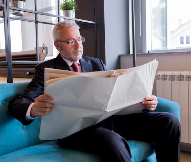 Älterer geschäftsmann, der auf sofalesezeitung im büro sitzt