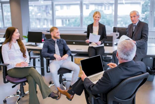 Älterer geschäftsmann, der auf stuhl mit dem laptop sitzt vor seinem team im büro sitzt