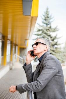 Älterer geschäftsmann, der durch telefon spricht