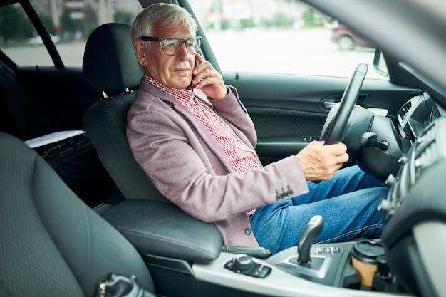 Älterer geschäftsmann, der ein auto fährt