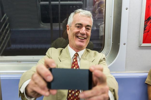 Älterer geschäftsmann, der ein selfie in der u-bahn-serie nimmt