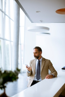 Älterer geschäftsmann, der handy im modernen büro verwendet