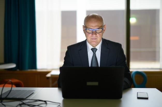 Älterer geschäftsmann, der mit laptop arbeitet, während er im büro sitzt