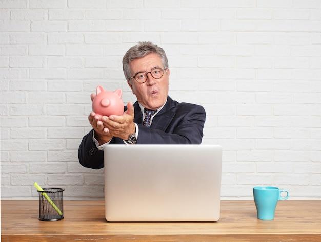 Älterer geschäftsmann, der mit seinem laptop arbeitet und ein schweinchen hält