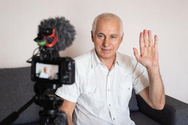Älterer geschäftsmann, der seine hand winkt, während er ein video für ein blog zu hause unter verwendung der videokamera macht