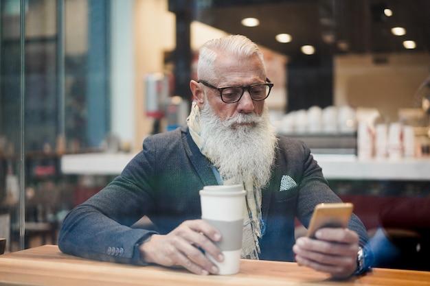 Älterer geschäftsmann, der smartphone-app beim kaffeetrinken in der cafébar verwendet