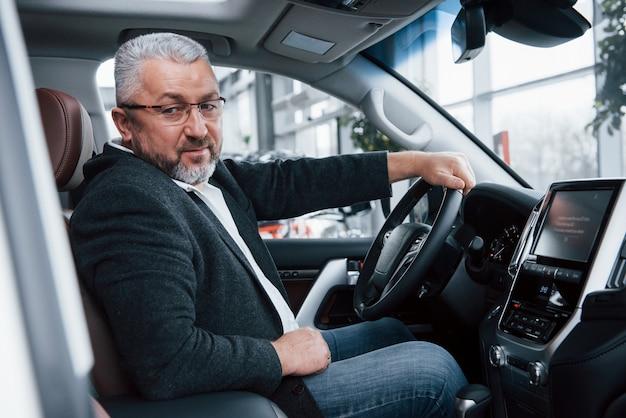 Älterer geschäftsmann in der offiziellen kleidung, die neues luxusauto im autosalon versucht