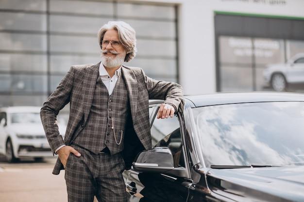 Älterer geschäftsmann in einem autohaus, der ein auto wählt