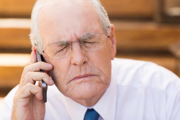 Älterer geschäftsmann mit geschlossenen augen, während am telefon sprechen