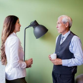 Älterer geschäftsmann und reife geschäftsfrau, die während eines bruches zusammenwirken