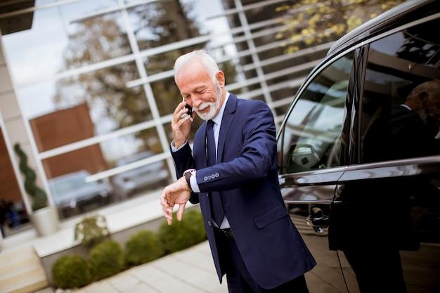 Älterer geschäftsmann unter verwendung des handys nahe auto