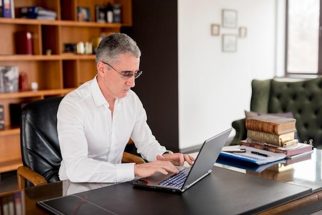 Älterer geschäftsmann unter verwendung seines laptops
