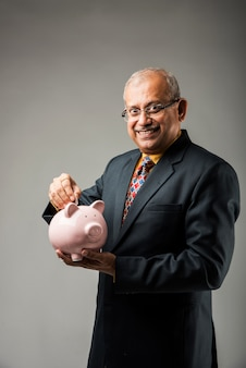 Älterer glücklicher indischer geschäftsmann, der sparschwein hält und münze hineinlegt. auf grauem hintergrund isoliert