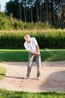 Älterer golfspieler im sandfang