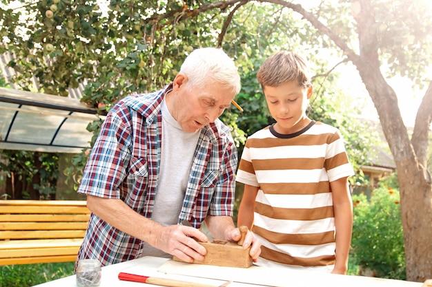 Älterer grauhaariger älterer mann und jugendlicher junge stehen mit werkzeugen am tisch. großvater lehrt seinen enkel schreinerei.