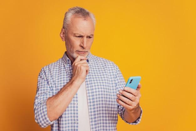 Älterer grauhaariger bärtiger mann isoliert auf gelbem hintergrund mit handy lesen post