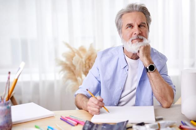 Älterer grauhaariger künstler mit bleistift, der hinter tisch sitzt, bereit, etwas zu malen, verschiedene werkzeuge, papier und andere materialien zum zeichnen habend