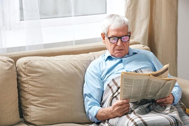 Älterer grauhaariger mann, der in eine karierte lesezeitung eingewickelt ist, während er sich auf der couch am fenster entspannt, während er zu hause bleibt