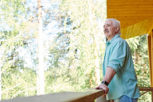 Älterer grauhaariger mann im blauen hemd, der auf terrasse durch hölzerne geländer am sonnigen tag steht und natürliche landschaft betrachtet